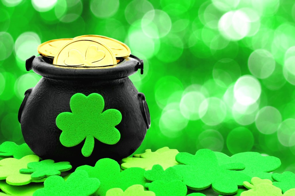 st patricks day pot of gold and shamrocks over a green background