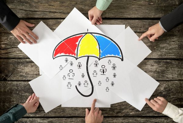 Safety and life insurance concept - six hands assembling a colourful umbrella sheltering many people icons drawn on white papers.