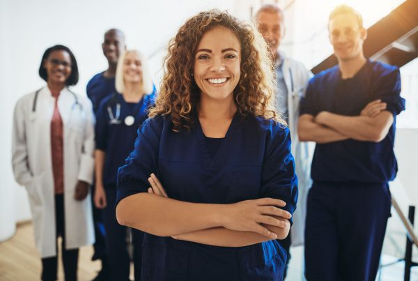Young female doctor smiling while standing in a hospital corridor with a diverse group of staff in the background