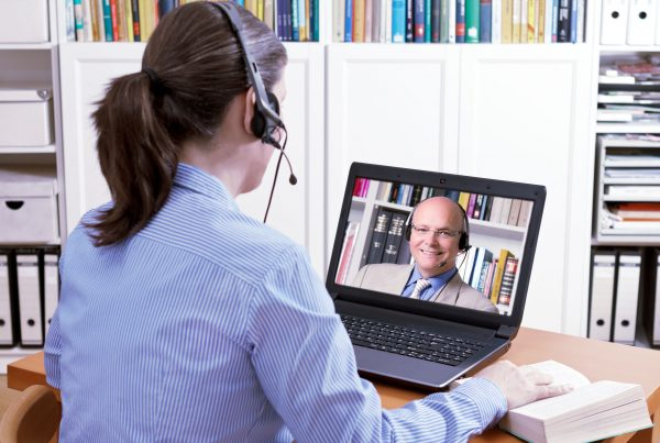 Woman with a headset in front of her laptop and a book making an online video call with her friendly teacher, text space, e-learning concept